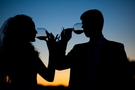 Bride and groom drink wine at sunset photo