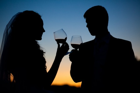 Bride and groom drinking wine at sunset photo