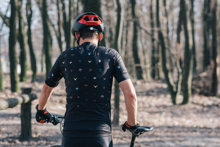 male athlete mountainbiker with bicycle along a forest trail. in forest mist
