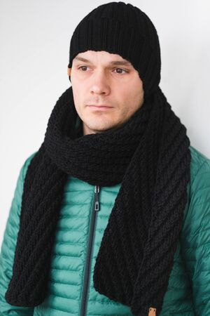 Cool man in winter fashion. Wearing scarf and knit hat