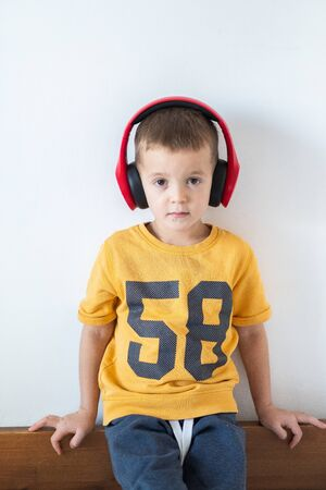 Young boy listening to music on headphones on white background