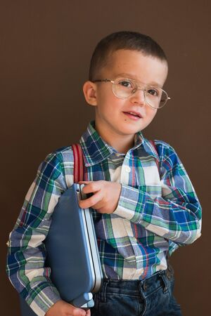 Portrait of a cute serious boy using a laptop. Child in glasses with a laptop