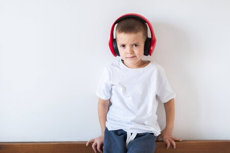 Boy in white t-shirt with headphones isolated on white background
