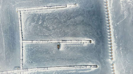 frozen in winter ice lake, docked in pier, aerial top down view