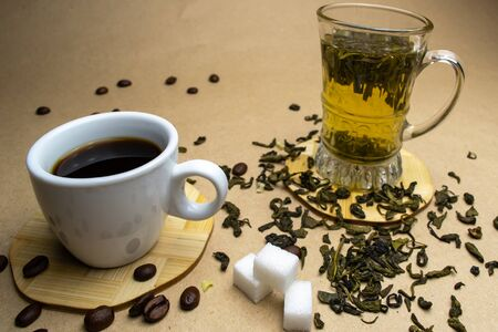 A cup of coffee with grains and a glass cup of green tea on a stand with dried leaves of green tea and sugar cubes Zdjęcie Seryjne - 140206646