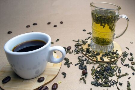 A cup of coffee with grains and a glass cup of green tea on a stand with dried leaves of green tea Zdjęcie Seryjne