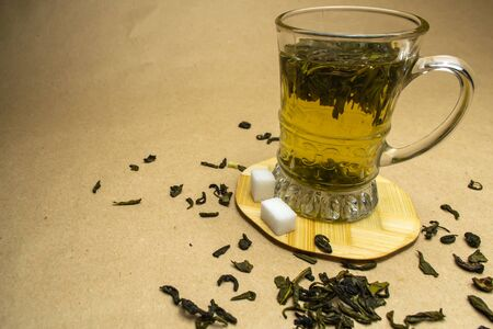 Glass cup of green tea on a stand with sprinkled green tea and sugar cubes