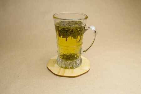 Glass cup of green tea on a stand