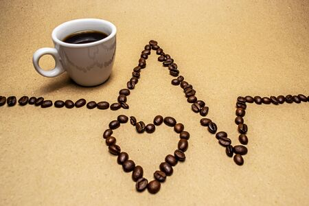 Heart and zigzag from coffee beans and a white cup on a beige background