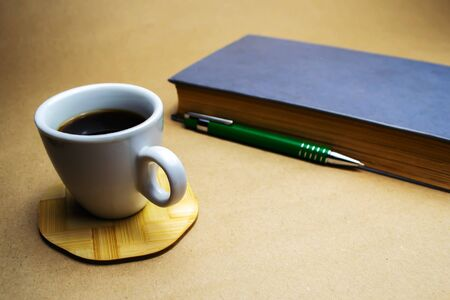 White cup with coffee on a wooden stand with a book and a green ballpoint pen on a beige background