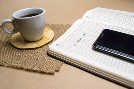 A cup of coffee on a napkin, a notepad with the inscription I miss you, mobile phone