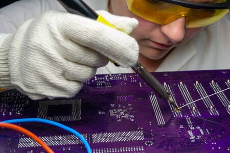 Female master solders a motherboard with a soldering iron