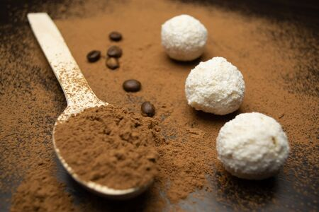 Three white truffles, a wooden spoon with cocoa, coffee grains on a black background