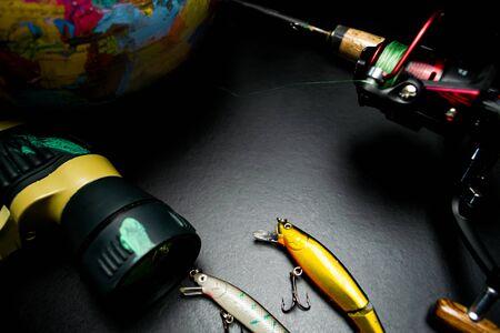 Fishing tackle, binoculars, globe, on black background