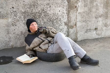 Homeless dirty woman sitting asking for help and reading a book