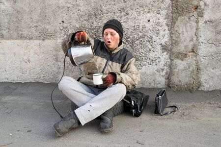 Homeless dirty woman sits under the wall and pours herself tea