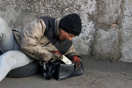 Homeless dirty woman lies on the ground and found a dollar in her purse