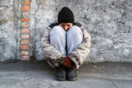Dirty homeless woman sitting under a gray wall hugging her legs
