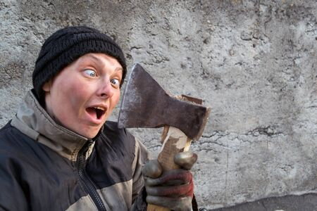 Homeless woman with an axe in her hands. Grey background Stock Photo