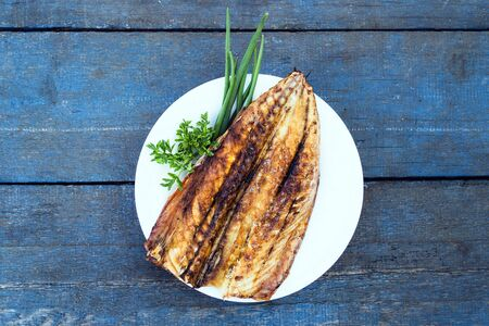 Baked mackerel fish on a white plate on a blue wooden table
