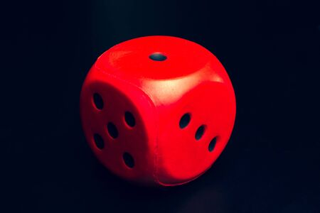 Big dice of red color on a black background
