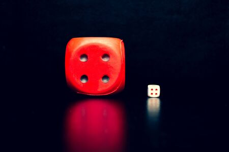 Big red dice next to a small white dice on a black background