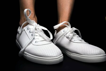White sneakers are dressed on legs on a black background. Sport shoes