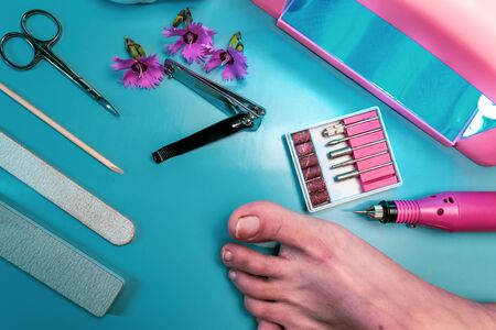 Preparing nails for applying gel polish. Set of cosmetic tools for manicure and pedicure on a black background. Gel polishes, nail files and tongs and a lamp.