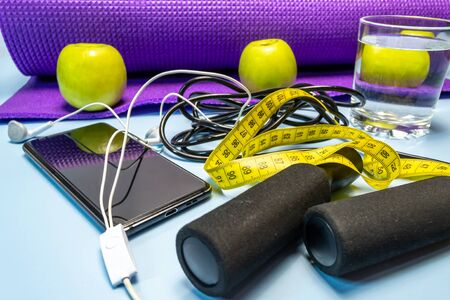 Yoga mat and glass of water close-up. Sports equipment, green apples and a jump rope.