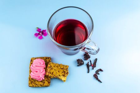 Hibiscus tea cup and two cookies on a blue background 版權商用圖片