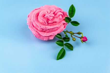 Beautiful pink decorative edible marshmallow roses, real rose branch, on a blue background