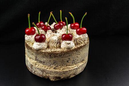 Tiramisu cake decorated with cherries, on a black background.