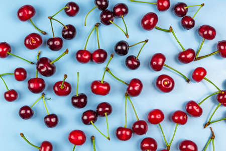 Red juicy cherries on a blue background
