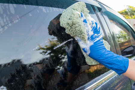 Car wash, woman in blue gloves and a sponge with foam wipes the car