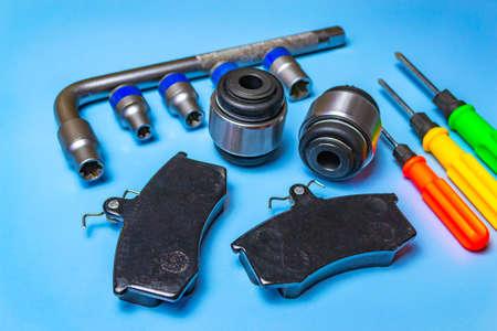 Auto parts, brake discs, pads. Salintblok car, starry auto keys, brake pads and screwdrivers on a blue background