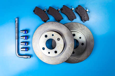 Auto parts, brake discs, pads and star auto keys on a blue background Stock fotó
