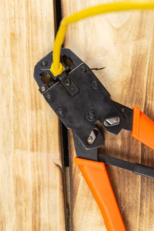 Orange crimping tool and wire on wooden background