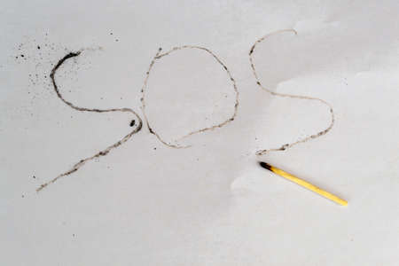 SOS inscription with a burnt match on a sheet of paper