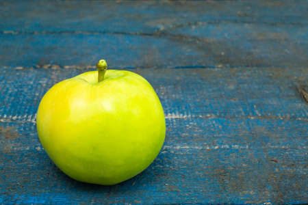 Green apple on blue background close up