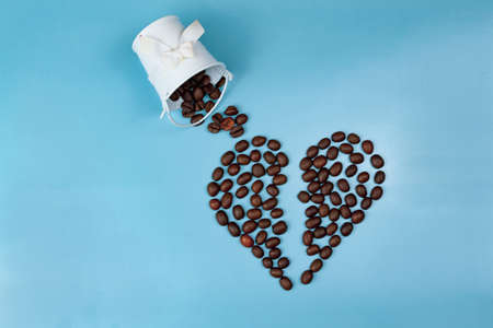 Broken heart made of coffee beans on a blue background close up