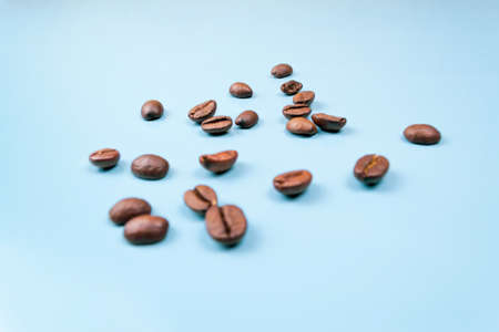 Coffee beans sprinkled on blue background close up Фото со стока