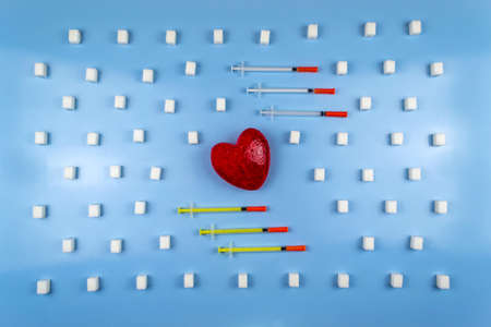 Heart and insulin syringes surrounded by sugar cubes. World Diabetes Day Stock Photo