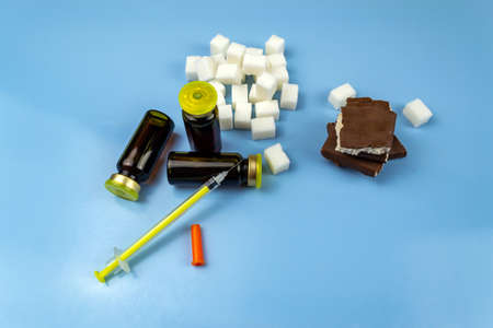 Insulin, syringe, sugar cubes and chocolate chunks, world diabetes day