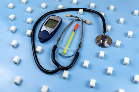 Digital blood glucose meter, stethoscope surrounded by sugar cubes. World Diabetes Day