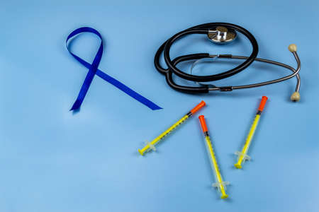 Stethoscope and insulin syringes, world diabetes day concept