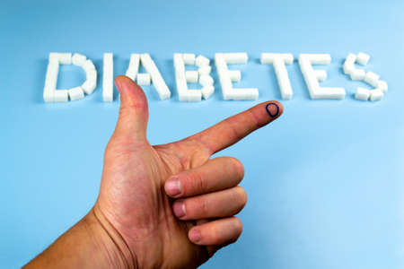 On the index finger - the diabetes icon - a blue circle, against the background of the inscription diabetes. World diabetes day concept Stock Photo