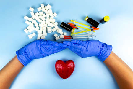 Hands in blue rubber gloves push off refined sugar, insulin World diabetes day concept Stock Photo