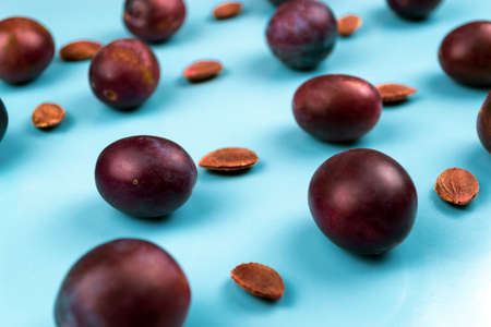 A lot of plums and pits on a blue background. Close-up
