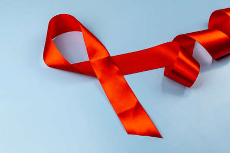 Red ribbon on blue background aids day