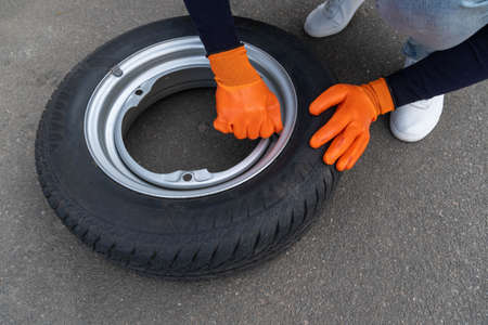 Close-up of a woman in orange gloves unscrews the nipple cover on a car wheel.
